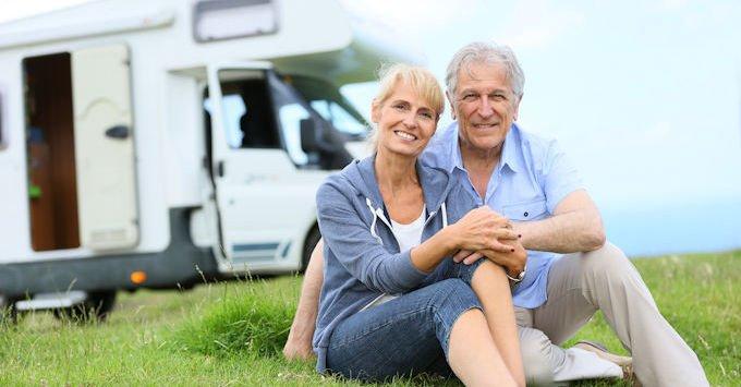 older couple sitting by camper